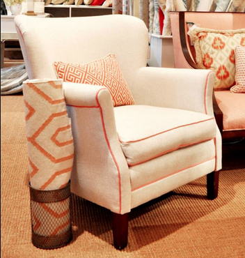 The pop of coral trim on this cream chair makes it a more interesting piece.
