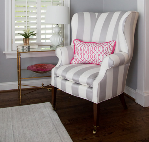 A bold gray and white armchair with a hot pink and white pillow. Look decorated by Diane Litz.
